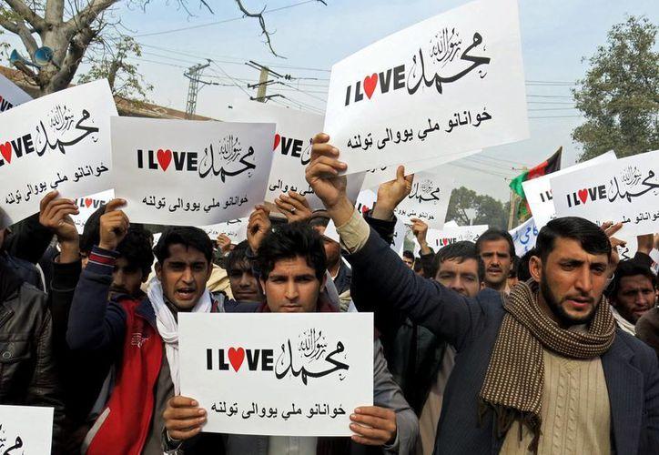 """Afganos sostienen carteles que decían: """"Amo al profeta Muhammad, Partido Solidaridad Juventud """", durante una protesta contra las caricaturas publicadas en la revista francesa Charlie Hebdo en la ciudad de Jalalabad , al este de Kabul , Afganistán. (Agencias)"""