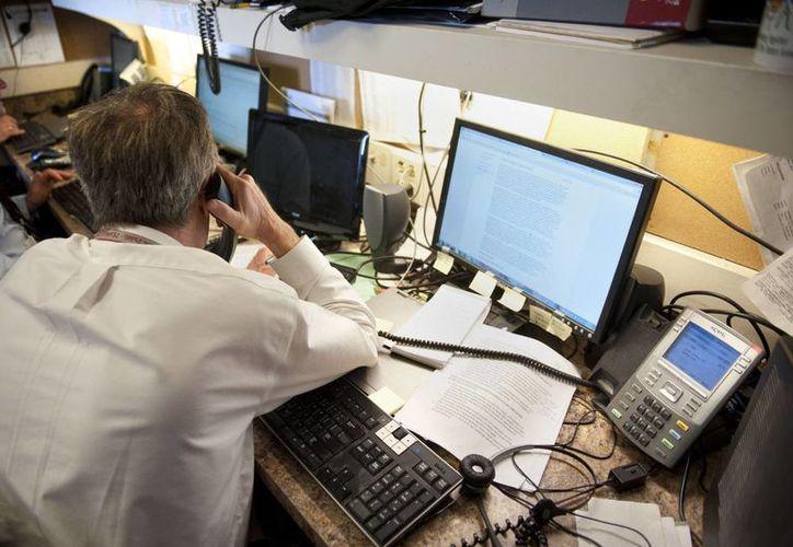 Reporteros de AP laboran en su espacio asignado en la sala de prensa del Capitolio, en Washington, DC. (AP)