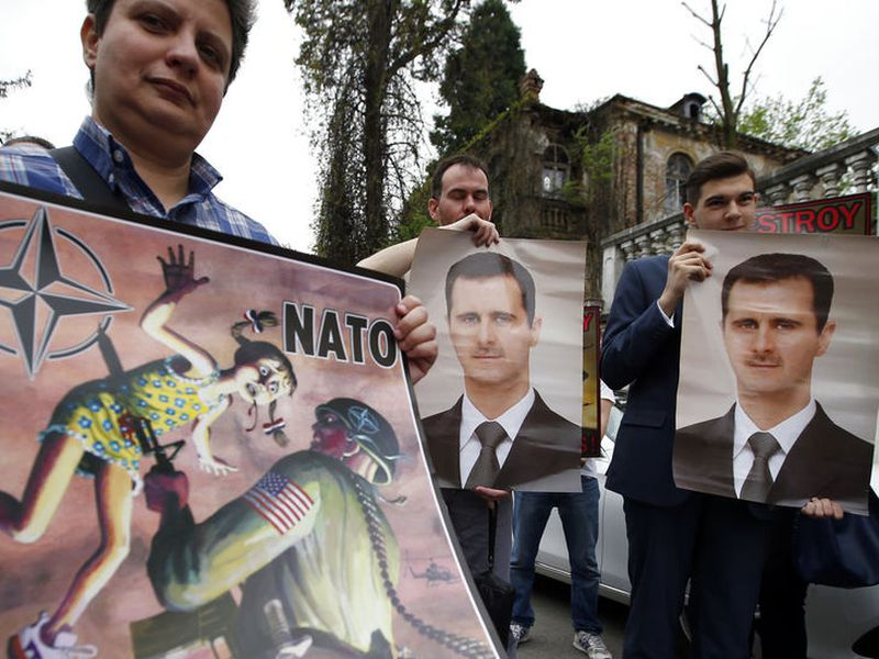 People hold pictures of Syrian President Bashar al-Assad and an anti NATO poster during a protest outside the Syrian embassy in Belgrade, Serbia, Sunday, April 15, 2018. A few dozen people took part in an anti-war rally opposing the military strikes by western countries in Syria. (AP Photo/Darko Vojinovic).