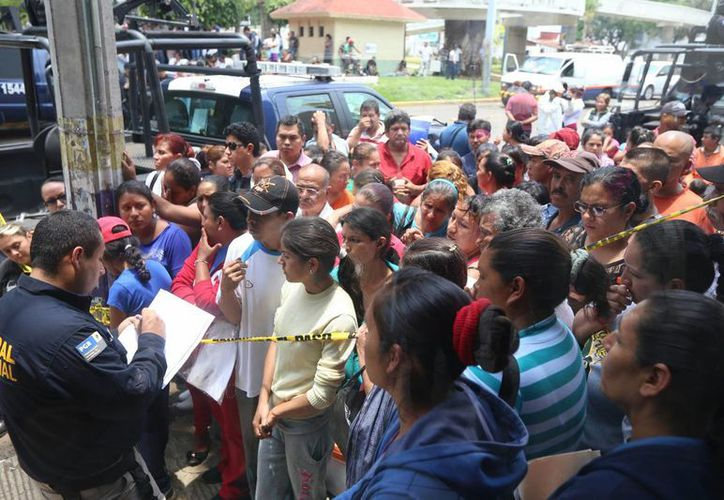 Decenas de familiares esperan en las instalaciones de 'La Gran Familia', en Zamora, información sobre los pequeños que estaban recluidos en el sitio. (EFE)