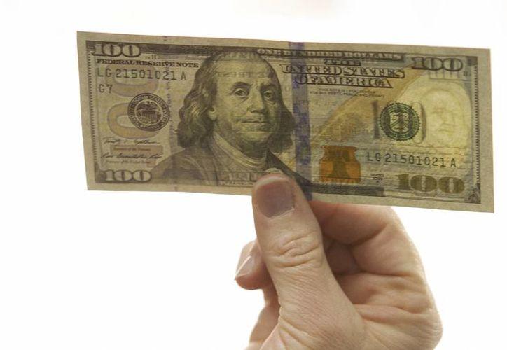 El dólar interbancario se vende en 15 pesos en promedio desde el pasado jueves. Imagen de un billete de 100 dólares (Notimex)