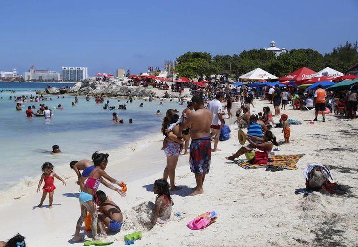 Los visitantes, acompañados de amigos y familia, arribaron a la playa. (Israel Leal/SIPSE)