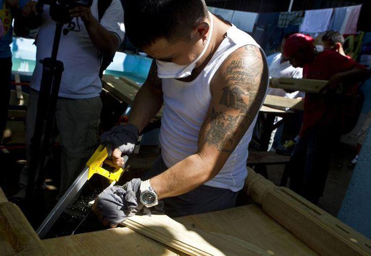Un pandillero de la Mara Salvatrucha corta madera en la cárcel de San Pedro Sula. (Agencias)