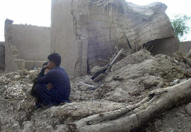 Varias personas permanecen junto a sus casas en ruinas tras el terremoto en Awaran, Pakistán. (EFE)