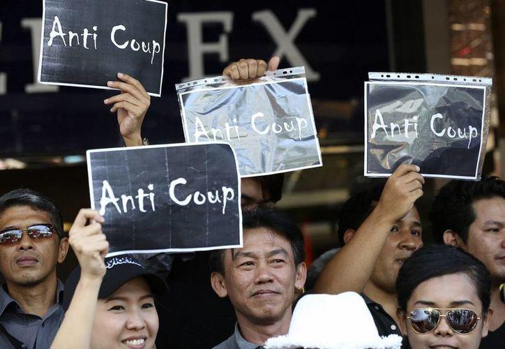 Manifestantes antigolpistas tailandeses sostienen pancartas durante una protesta frente a un centro comercial en Bangkok, Tailandia. (Agencias)