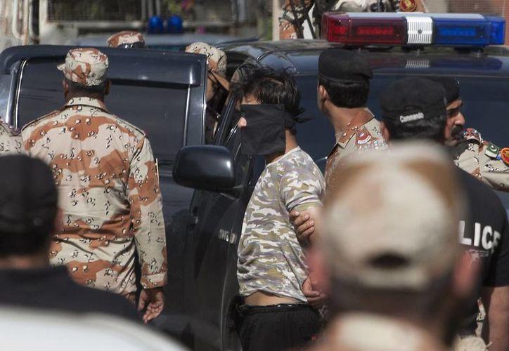 Agentes escoltan a un sospechoso luego de un tiroteo en Karachi, Paquistán, el lunes 6 de febrero del 2017. Un guardia de seguridad mató a tiros a un diplomático afgano el lunes, dentro del consulado, en Karachi. (AP/Shakil Adil)