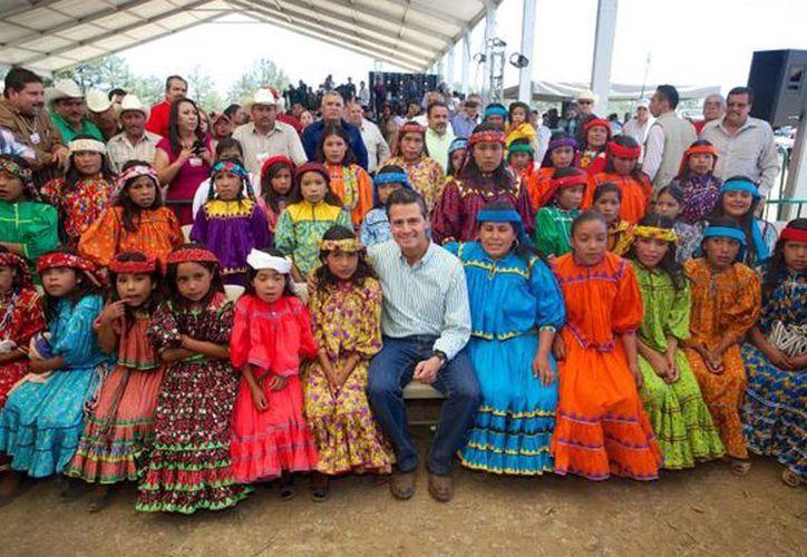 El presidente Enrique Peña Nieto acompañado de diversos pobladores de la comunidad Otomí al conmemorar el Día Internacional de los Pueblos Indígenas. (Tomada de @PresidenciaMX )