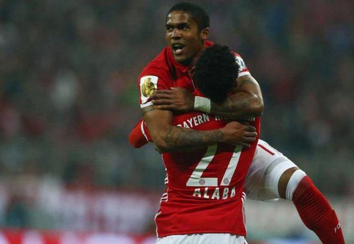 Douglas Costa celebra con Thiago su gol ante Wolfsburgo, que fue suficiente para que Bayern avanzara a la ronda de los ocho mejores. (marca.com)