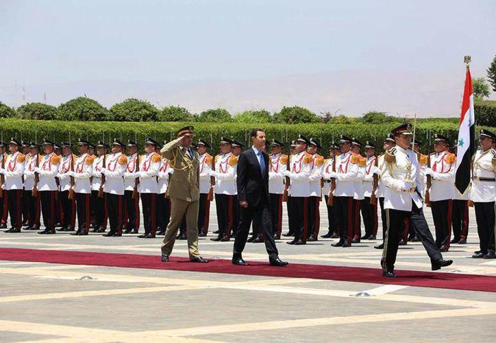 El presidente sirio Bashar al Assad (de negro) durante su tercera toma de protesta frente al palacio presidencial. (Foto: AP)