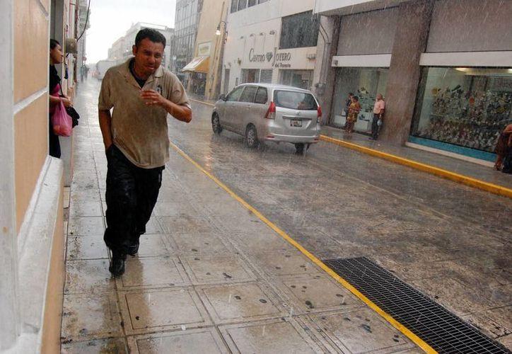 Las lluvias vespertinas sorprendieron a los transeúntes. (Wilberth Arguelles/SIPSE)