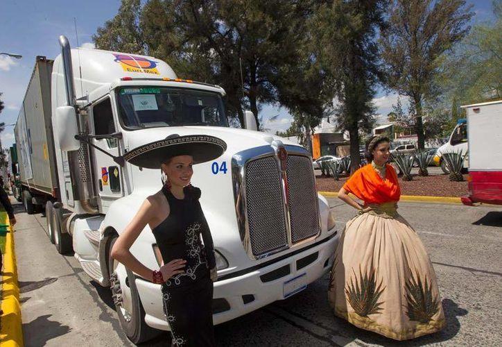 Dos jóvenes ataviadas con vestidos típicos frente al convoy que partió con el embarque de tequila a Chbina, este viernes, en Zapopan, Jalisco. (AP)