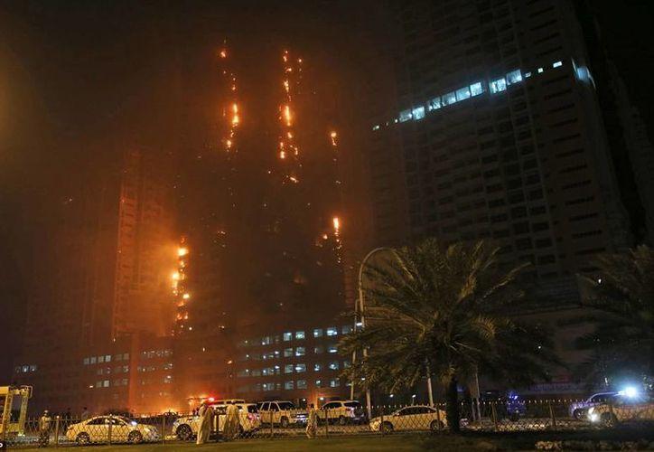 Cientos de curiosos se amontonaron para observar el edificio en llamas. (AP)