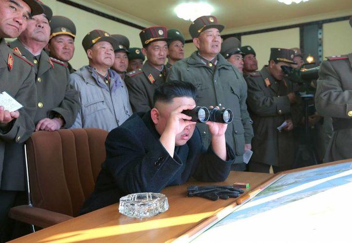 Foto sin fechar del líder norcoreano, Kim Jong un (c), junto a oficiales durante ejercicios de artillería con islas fronterizas surcoreanas. (EFE)