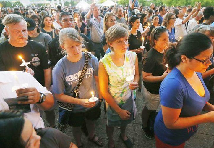 Cientos de personas participan en una vigilia en el Ayuntamiento de Dallas, en memoria a los 5 policías que fueron muertos a tiros y los heridos en un tiroteo ocurrido la noche del jueves pasado. (AP Foto/Tony Gutiérrez)