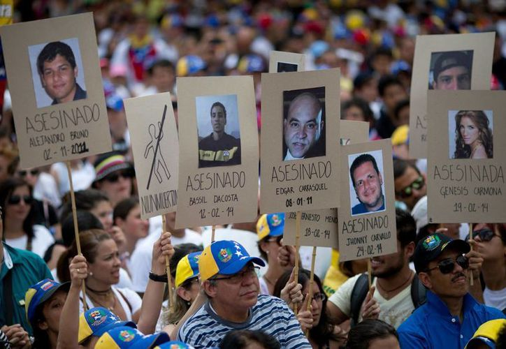 Manifestantes sostienen pancartas con las fotografías de venezolanos que murieron en las protestas de la últimas semanas durante una manifestación opositora en Caracas, Venezuela. (Agencias)