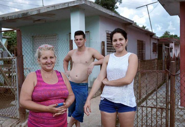 Olea Lastre (izq), cuyo esposo e hijo se fueron a Estados Unidos, posa para una foto con su hija Olia Cárdenas y un amigo de la familia afuera de su casa en el vecindario Porvenir de Camagüey, Cuba. (Agencias)