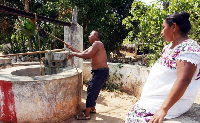 Para atender esta situación este año se continuará el trabajo de rescate de cenotes y la rehabilitación de humedales. Imagen de un hombre recolectando agua desde un pozo. (Milenio Novedades)