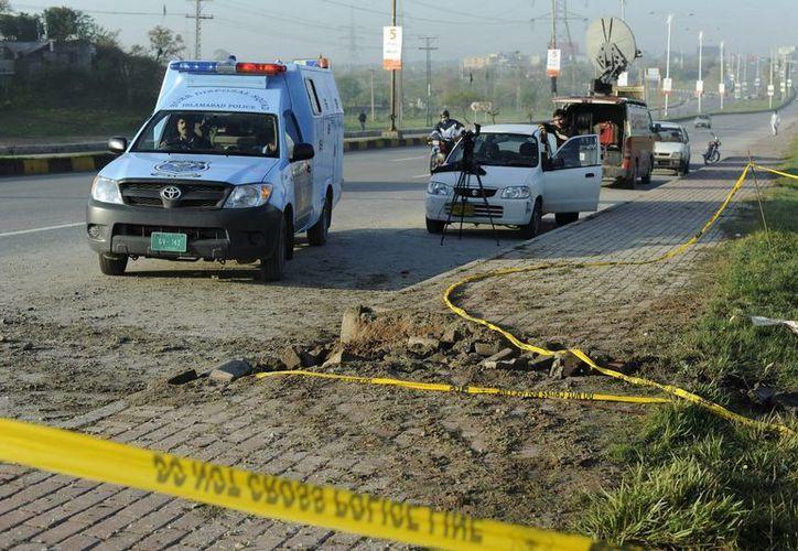 La policía inspecciona la zona donde se produjo el atentado con explosivos al paso del convoy del expresidente Musharraf en Islamabad. (EFE)