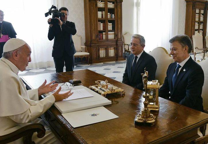 El Papa Francisco habla con el presidente de Colombia, Juan Manuel Santos (der), y el ex presidente Álvaro Uribe durante una reunión en el Vaticano. (Vincenzo Pinto/Pool Photo via AP)