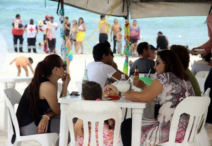 El Programa Vacacional y Turístico 2015 operará en toda la zona costera de Yucatán. Imagen de un grupo de comensales en las orillas de la playa de Progreso. (Milenio Novedades)