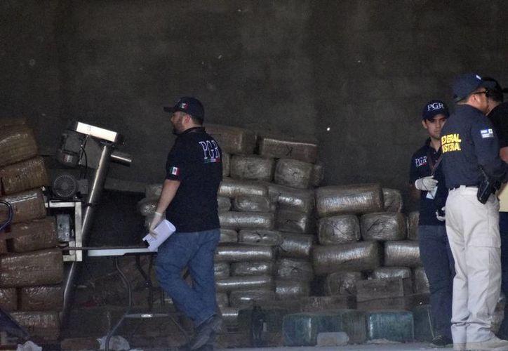 Elementos del Ejército Mexicano resguardan una bodega mientras agentes federales decomisan marihuana dentro de una bodega en el DF. (Notimex)