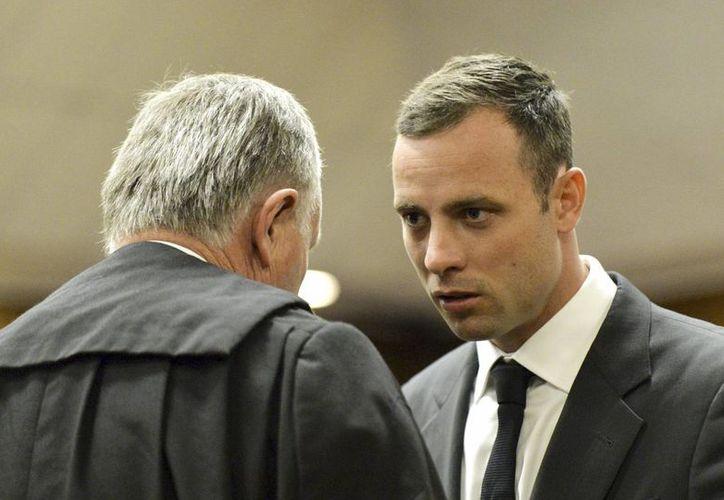 El atleta paralímpico Oscar Pistorius conversa con uno de sus abogados en el Tribunal Supremo en Pretoria, Sudáfrica. (EFE)