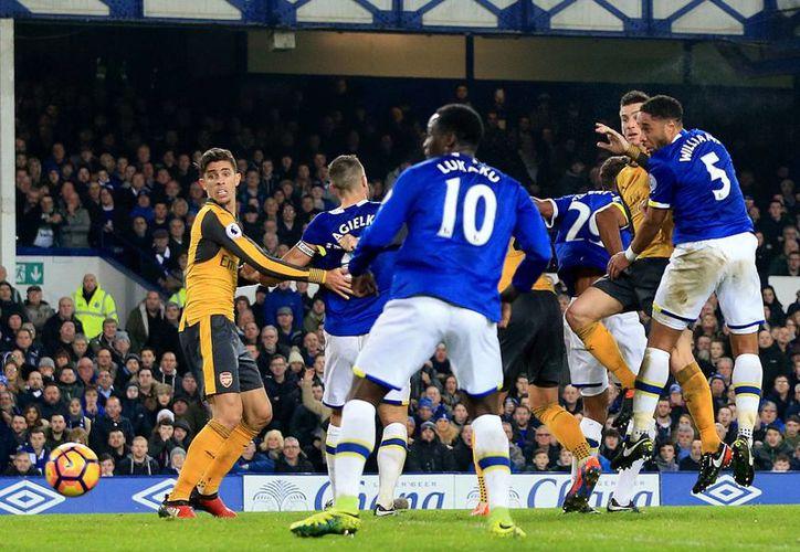 Con un gol de Ashley Williams (d) casi al final, Everton ganó 2-1 al Arsenal y le quitó la oportunidad de acercarse al Chelsea, líder de la Liga Premier. (AP)