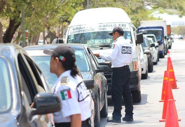 Integrantes del Grupo Escudo de la SSP entregan a los automovilistas folletos con recomendaciones para evitar accidentes. (SIPSE)