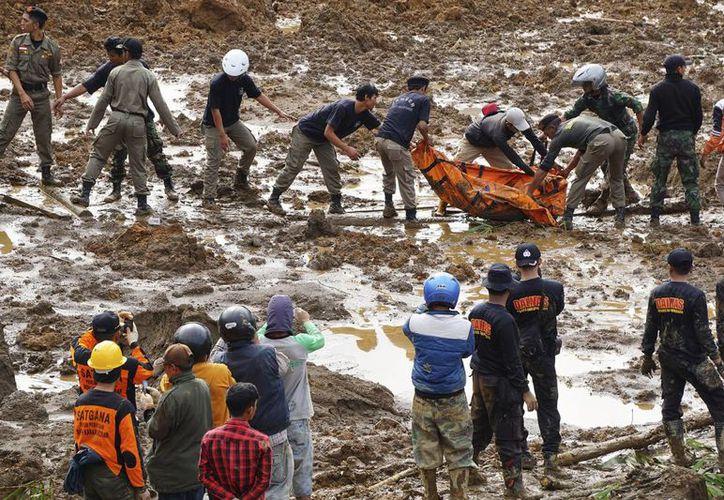 Trabajadores remueven de entre los escombros el cuerpo de una de las víctimas de un alud en Jemblung, Indonesia. (Foto: AP)