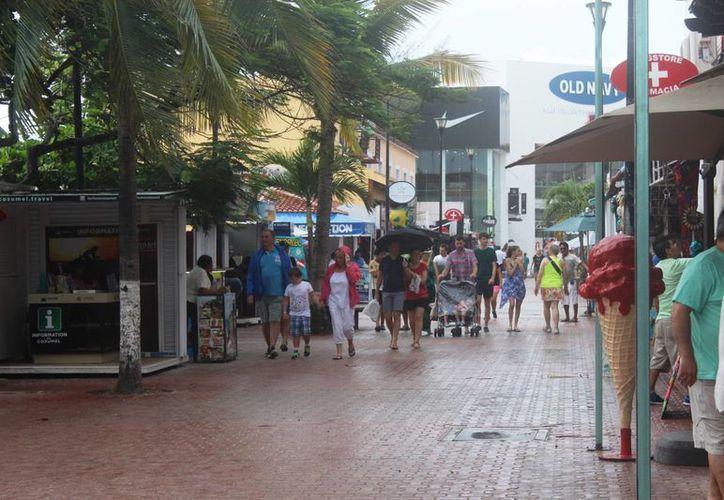 Las lluvias no impidieron que los paseantes recorrieron la Quinta Avenida de Playa del Carmen ayer. (Octavio Martínez/SIPSE)