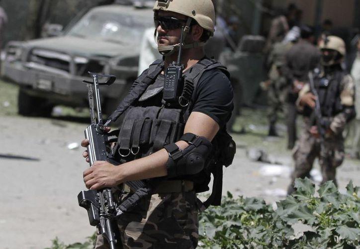 Miembros de las fuerzas afganas de seguridad resguardan el lugar donde se registró una explosión cerca de la Comisión Afgana Independiente de los Derechos Humanos en Kabul, Afganistán. (Agencias)