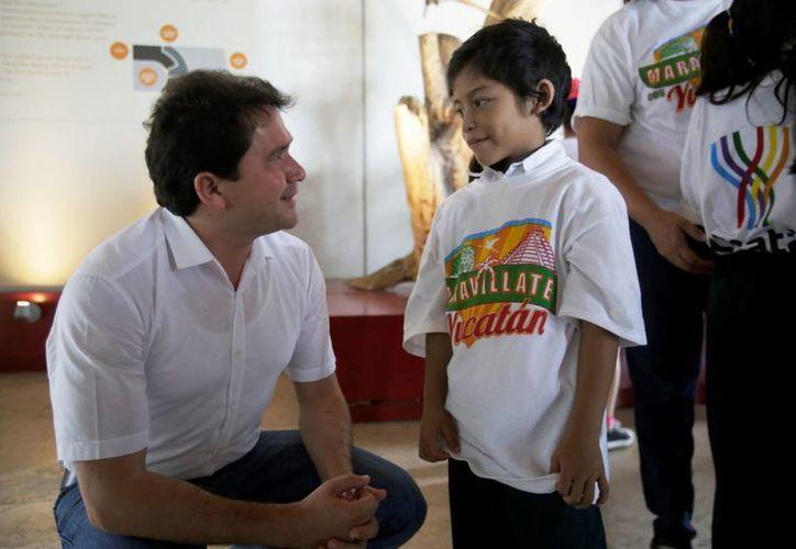 El niño Fernando Enrique con el titular de Sedesol, Mauricio Sahuí, en un recorrido en el Gran Museo del Mundo Maya. (Foto cortesía del Gobierno estatal)