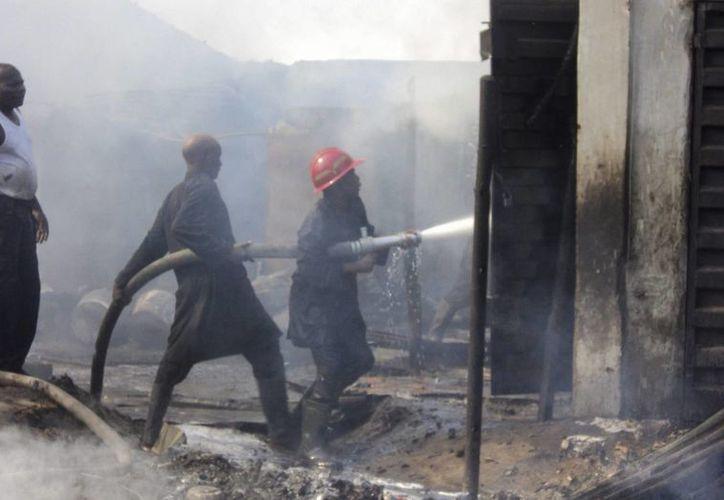 El incendio en la estación de autobús de hoy mató a casi 70 personas. En febrero de 2013,  un atentado bomba en el mercado Gamboru en Nigeria mató a cientos de personas. Imagen de bomberos nigerianos al tratar de apagar el incendio en aquella ocasión. (EFE/Archivo)