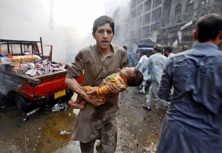 Un hombre carga a un niño herido por la explosión de un coche bomba en la ciudad de Peshawar, Pakistán. (Agencias)