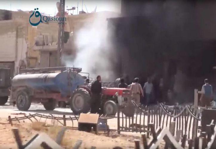 Imagen tomada de un video que muestra a un grupo de sirios reunidos entre los escombros de un edificio atacado por Rusia. (Agencias)