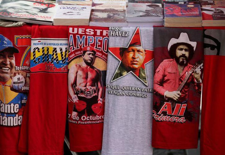 Camisetas con imágenes manipuladas del presidente Hugo Chávez, junto con una con la imagen del cantante popular Alí Primera, en un mercado en Caracas. (Agencias)