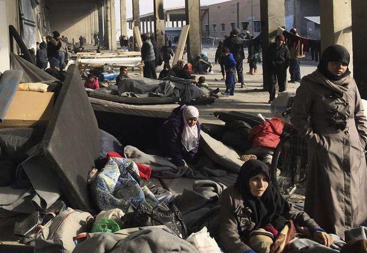 Imagen distribuida por el Comité Internacional de la Cruz Roja (ICRC), muestra a ciudadanos sirios desplazados del este de Alepo reunidos en un albergue colectivo, en la localidad de Jibreen, en Siria. (ICRC vía AP)