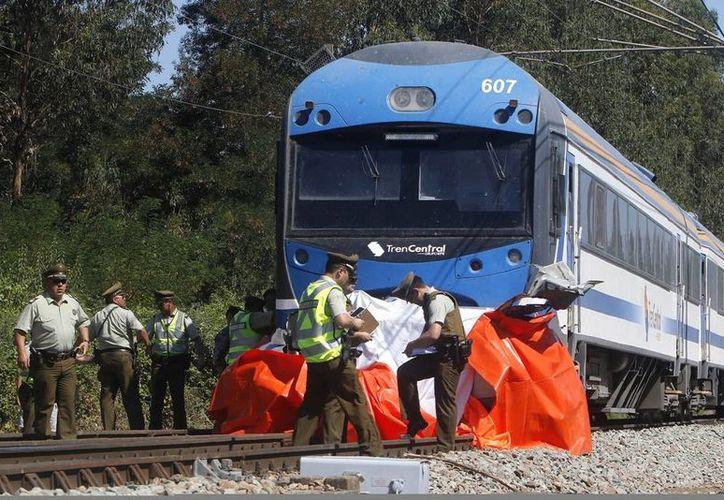 Miembros de la policía chilena trabajan en el lugar del accidente después de que un tren arrollara a un vehículo en la comuna de San Javier de la ciudad de Talca. (EFE)