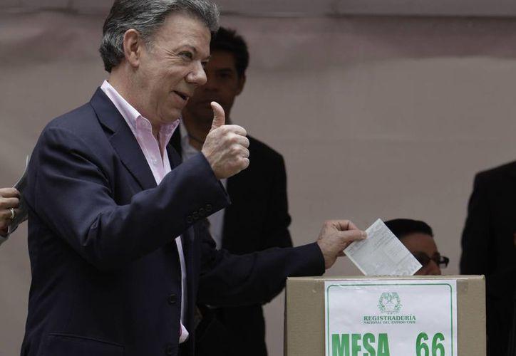 El presidente de Colombia, Juan Manuel Santos, emite su voto este domingo, durante la segunda vuelta electoral en el país sudamericano. (AP)