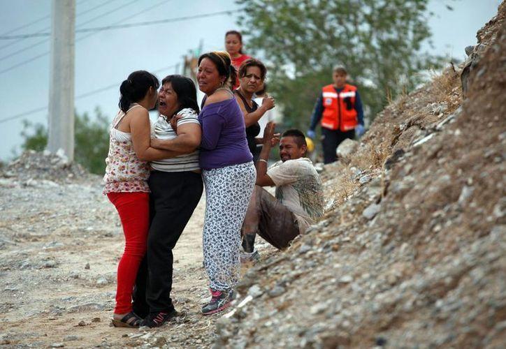 Imagen de los familiares de la mujer, quienes llegaron al lugar donde había ocurrido el derrumbe. (Reuters)