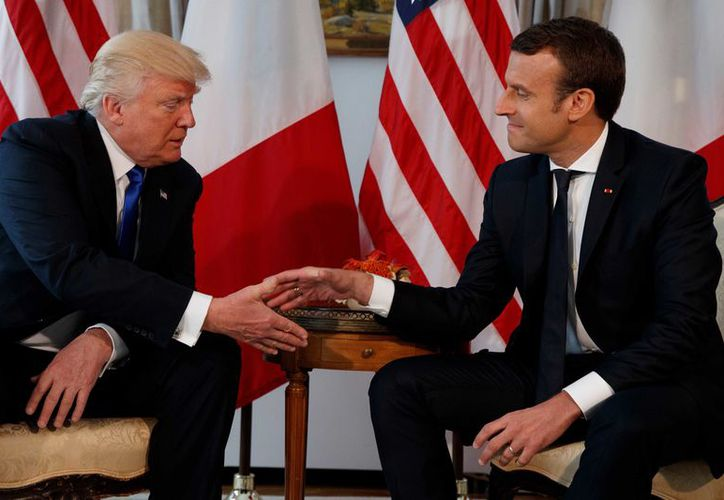 US President Donald Trump, shakes hands with French President Emmanuel Macron. (AP)