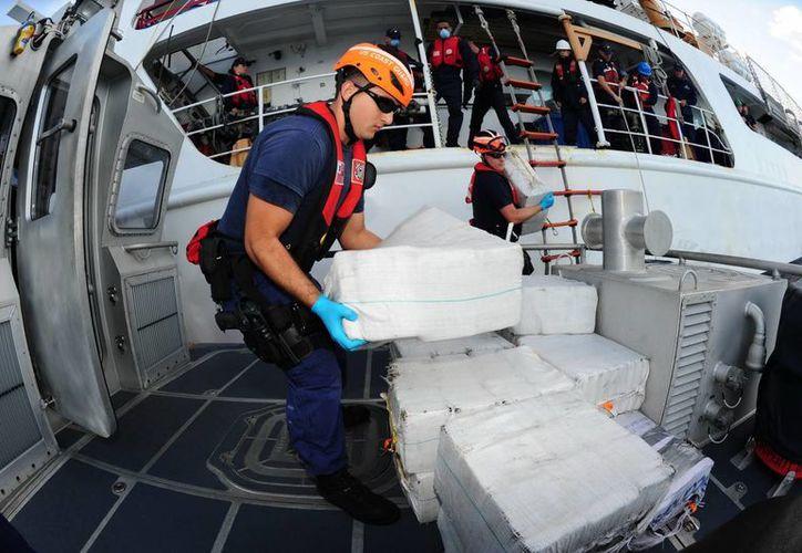 Foto cedida Guardia Costera de EU donde aparecen oficiales descargando parte de los 18 fardos con 635 kilos de cocaína incautados en el Caribe. (EFE/Suboficial Jon-Paul Ríos/U.S. Coast Guard)