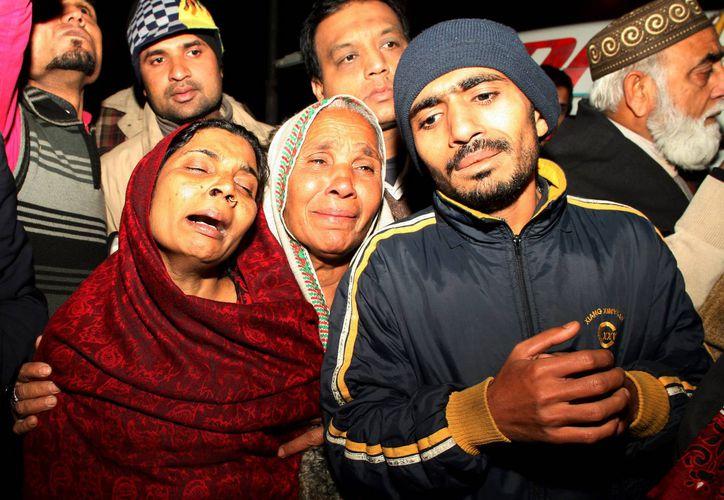 Personas lloran la muerte de sus familiares después de un incendio en un edificio, en Lahore, Pakistán. (Agencias)