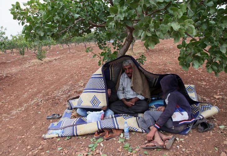 Refugiados sirios descansan, luego de cruzar la frontera con Turquía. El éxodo de ciudadanos de Siria aumenta al 'únisono' con los bombardeos por la guerra civil. (AP)