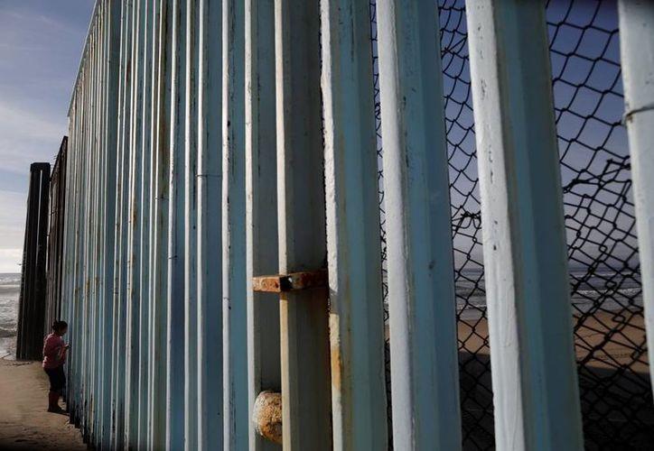 Muchos mexicanos aseguran que a pesar del enorme muro que ordenó construir el presidente Trump en la frontera, los indocumentados encontrarán la forma de cruzar a EU. (AP/Gregory Bull)