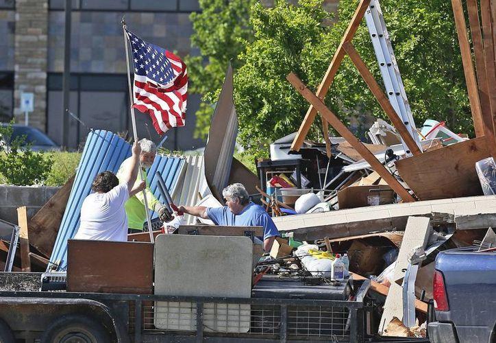 Ciudadanos de Oklahoma recogen sus pertenencias al tiempo de izan la bandera de Estados Unidos. (AP / S. Ogrocki)