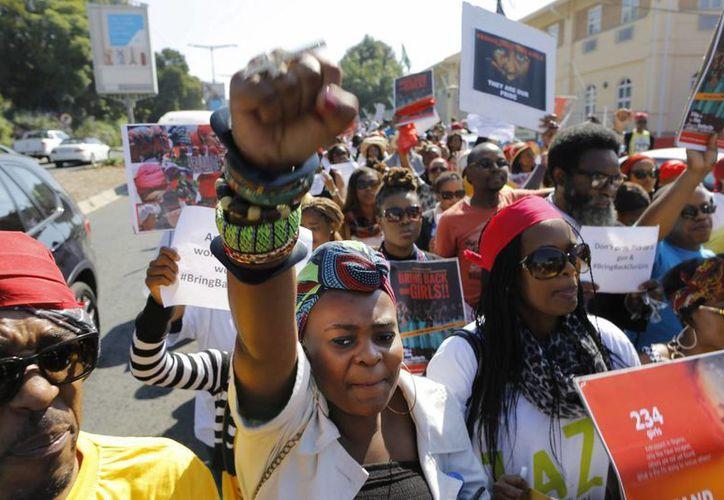 """Un grupo de activistas muestra pancartas en las que se puede leer """"traer de vuelta a nuestras niñas"""". (EFE)"""