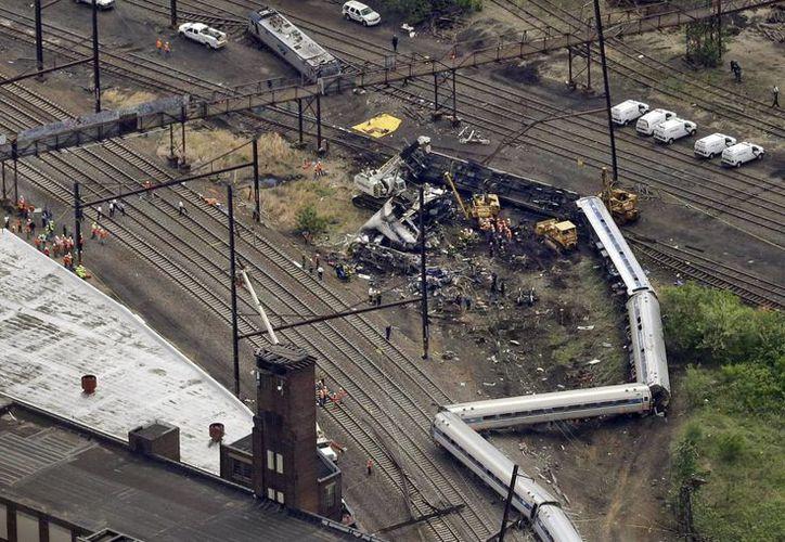 Personal de emergencia tranbaja en la escena del descarrilamiento de un tren de pasajeros en Filadelfia. (Agencias)