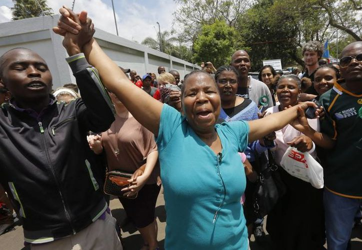 Varias personas cantan y bailan para mostrar su respeto al expresidente sudafricano Nelson Mandela frente a su última residencia en Johannesburgo, Sudáfrica. (EFE)