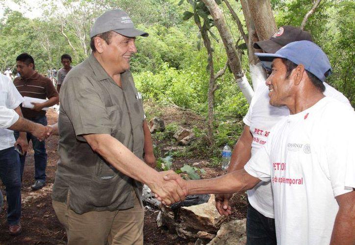 Carlos Berlín (i), de Semarnat, durante la entregas de apoyos de consolidación a proyectos productivos, herramientas de trabajo y apoyos económicos en Cuzamá.  (Foto cortesía del Gobierno estatal)